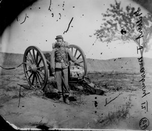 A Drummer Boy standing near a cannon.